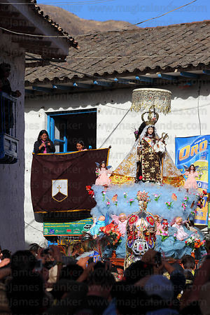 People watch main procession of Virgen del Carmen around village , Paucartambo , Peru