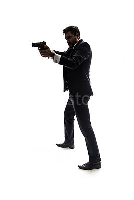 A mystery man in a suit, pointing a gun, in silhouette – shot from eye level.