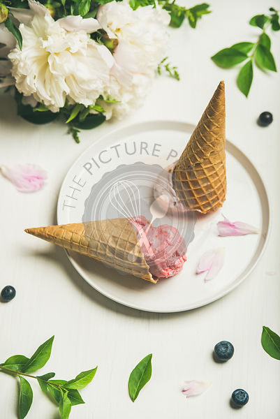 Pink strawberry and coconut ice cream scoops, sweet cones and peony flowers bouquet on plate