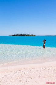 Tourist on sand bank in the lagoon of Aitutaki, Cook Islands