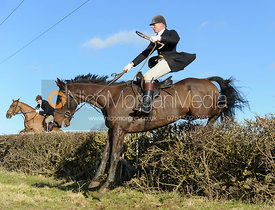 John Knowles jumping a hedge near Knossington Spinney - The Cottesmore at Furze Hill.