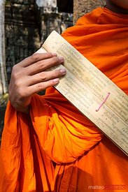 Buddhist monk holding ancient prayer book , Cambodia