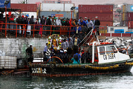Statue of St Paul is carried onto fishing boat at start of procession around port, St Peter and St Paul festival, Arica, Chile
