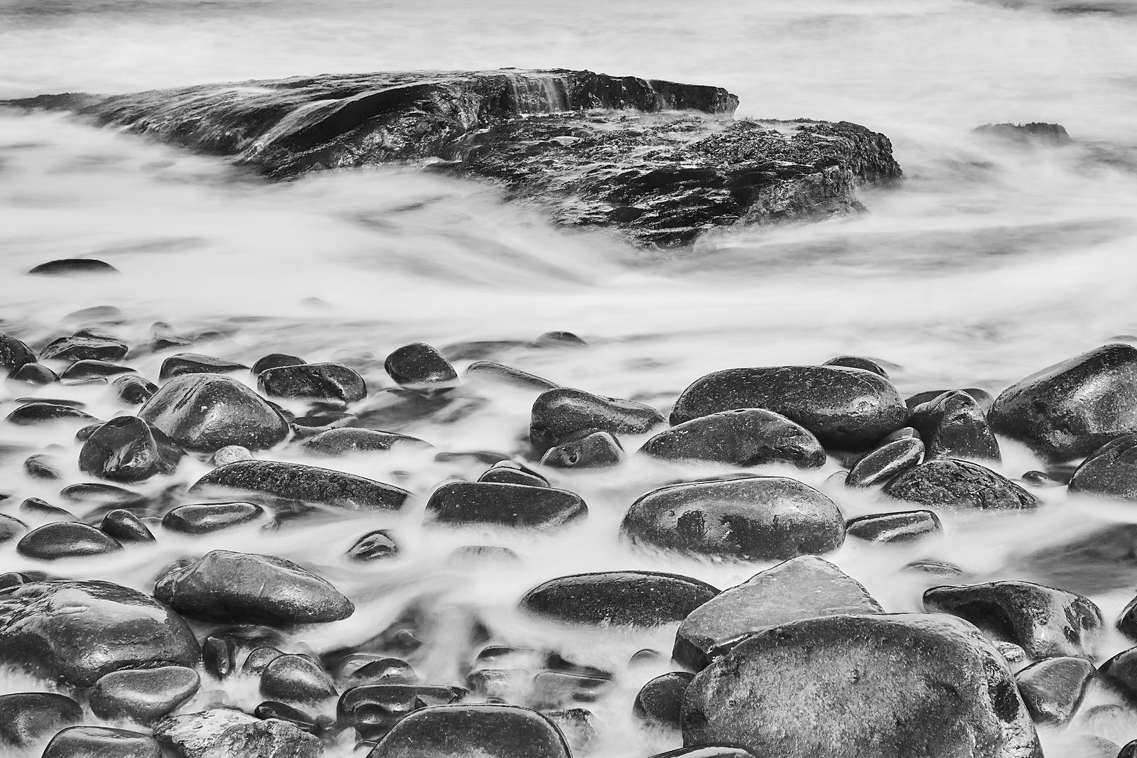 Rocks being washed by the waves in black and white