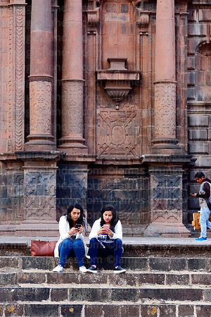 Girls chatting on smartphones in front of cathedral, Cusco, Peru