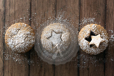 Three gingerbread fruit mince tarts dusted with powdered sugar on a wooden background.