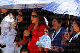 Hosting family (alferado) holding figures of baby Jesus during central mass for the Virgen de la Candelaria festival, Puno, Peru
