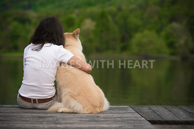 Woman sitting on a wooden pier with a dog