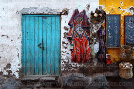 Rustic blue door and ponchos for sale at Pisac market, Sacred Valley, Peru