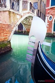 Close up detail of gondola's prow in a canal, Venice, Italy