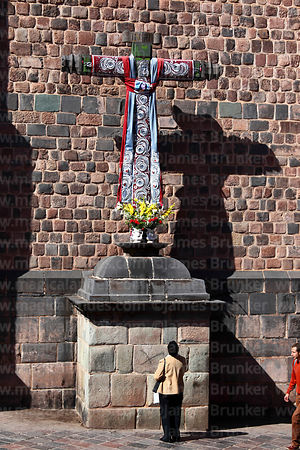Woman praying to cruz velakuy cross next to Santo Domingo church, Cusco, Peru
