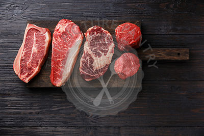 Variety of Raw Black Angus Prime meat steaks Blade on bone, Striploin, Rib eye, Tenderloin fillet mignon on wooden board copy space