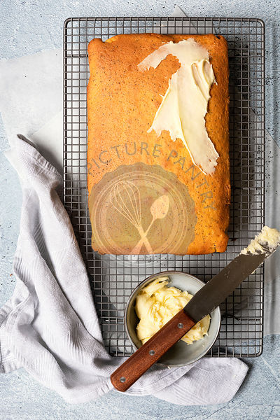 Orange and poppyseed cake partially spread with butter icing.