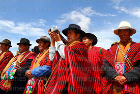 Local community leader using video camera to film dances at a festival, Umala, Bolivia