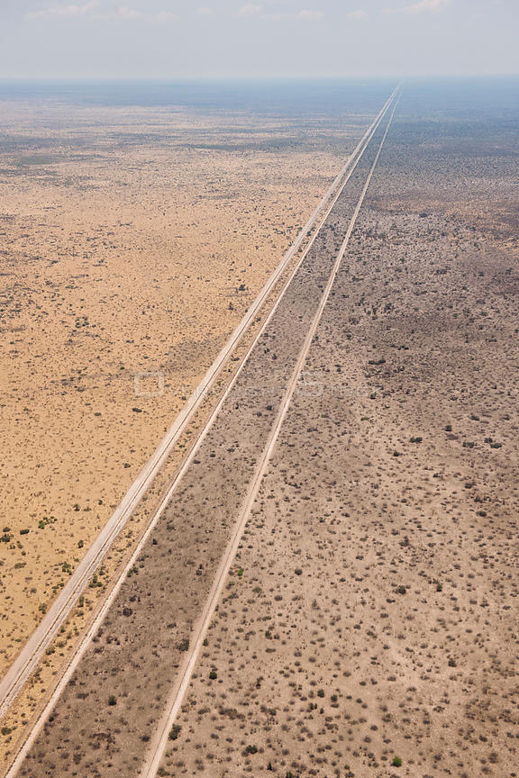 Aerial view of the results of a bushfire in the Kalahari desert, showing the road acting as a fire break, fires are normally lit by lightning in the beginning of the rainy season, Botswana, November.