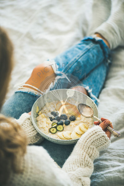 Woman in woolen sweater and shabby jeans eating vegan almond milk oatmeal porridge with berries