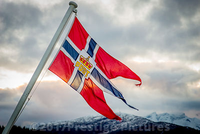 Flag flying on ship Carrying Norwegian Post with Mountains behind