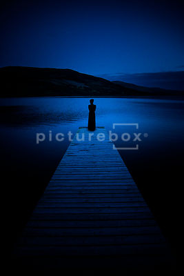 An atmospheric image of a woman in a dress, looking out over a lock / lake, from a wooden Jety, at night.