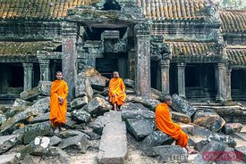 Monks sitting on temple ruins, Angkor, Cambodia