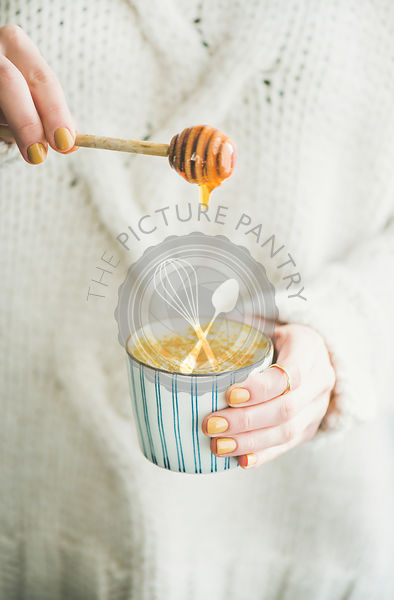 Turmeric latte or golden milk with honey in woman's hands