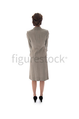 A 1940's / 1950's woman in a suit standing, looking away – shot from eye-level.