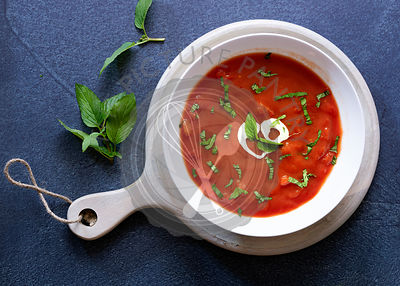 A bowl of chunky tomato soup with sour cream and chopped basil leaves on a wooden paddle board.