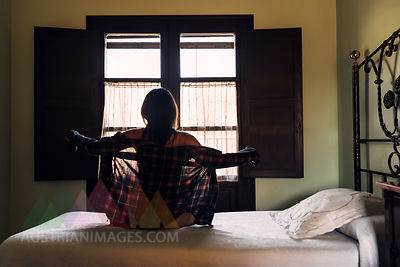 Back view of woman sitting on the bed next to a window putting on shirt