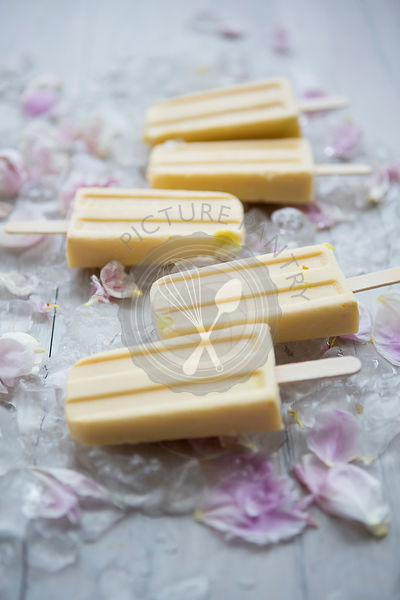 Mango Popsicle Lollies on Ice and Flowers