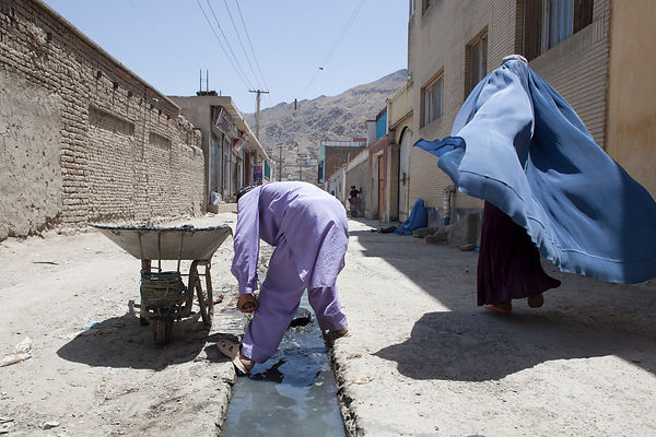 Bashir 13 ans nettoie le caniveau d'une rue commercante à Kaboul, Afghanistan / Bashir 13 years-old is cleaning the gutter of a market street in Kabul, Afghanistan