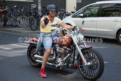 Motor Biker waving to the Camera from his Harley Davidson on the streets of Berlin