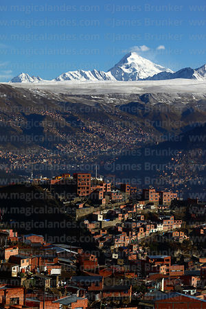 Houses on hillside below Jacha Kollo viewpoint and Mt Huayna Potosí after fresh winter snowfall, La Paz, Bolivia