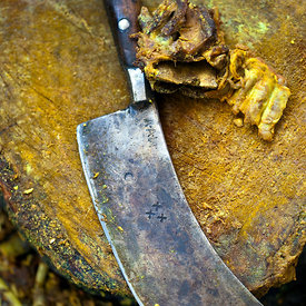 Detail of a cleaver on a chopping block in the kitchens at a Wazwan feast, Srinagar