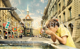 Boy drinks out of city fountain