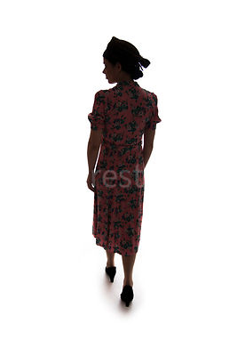 A silhouette of a 1940's woman in a flowery dress and hat, walking away – shot from eye-level.