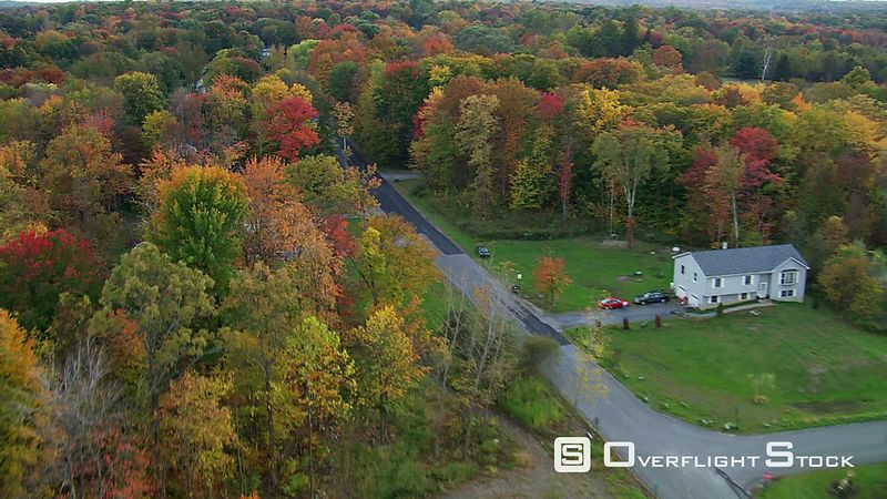 Flying over rural New England neighborhood among autumn woods