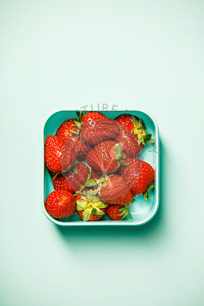 Container with fresh strawberry on pastel blue background. Flat lay, top view