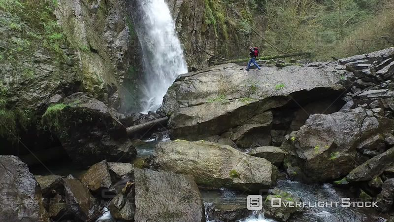 Backpacker Walking up Rocks to Waterfall Oregon USA Aerial Footage