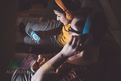 Couple listening to music with headphones and smartphone at home