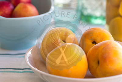 summer picnic of yellow peaches in a dish, with aqua bowls of nectarines and preserved peaches in background