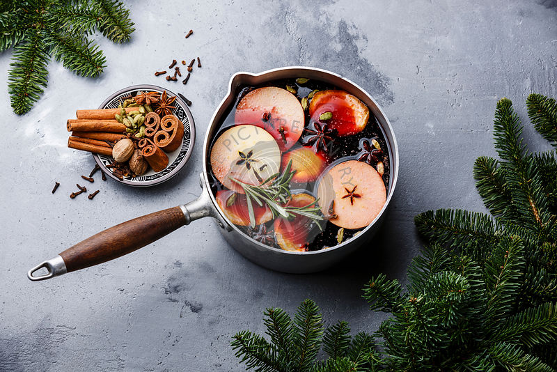Mulled wine hot drink with citrus, apple and spices in aluminum casserole and Fir branch on concrete background