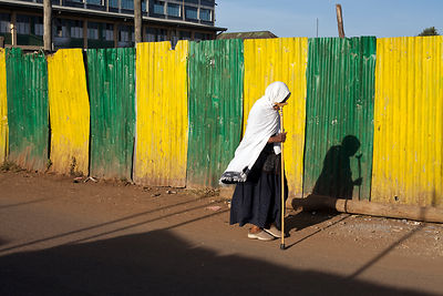 Ethiopia - Addis Ababa - A traditionally dressed woman walks with her stick past a yellow and green iron fence shielding a new development
