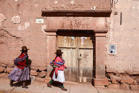 Local women walking past a colonial doorway with stone carvings, Maras, Cusco Region, Peru