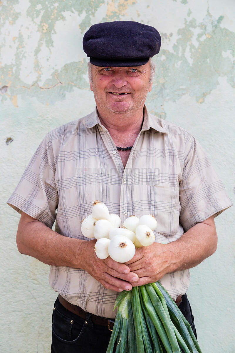 Portrait of a Market Seller Holding a Bunch of Onions