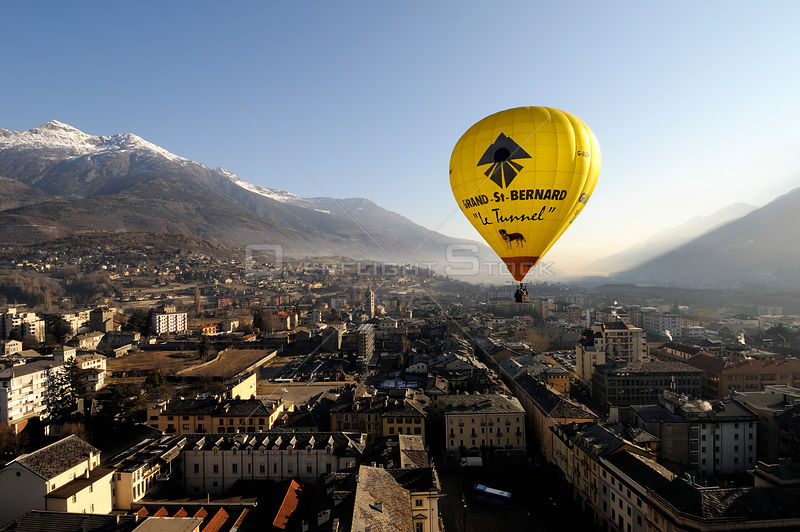 Hot air balloon in flight over the centre of Aosta City, northern Italian Alps