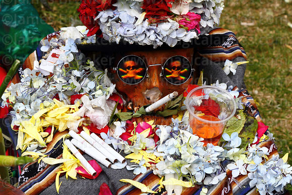 Skull wearing hologram sunglasses smoking a cigarette with fizzy drink offering, Ñatitas festival, La Paz, Bolivia