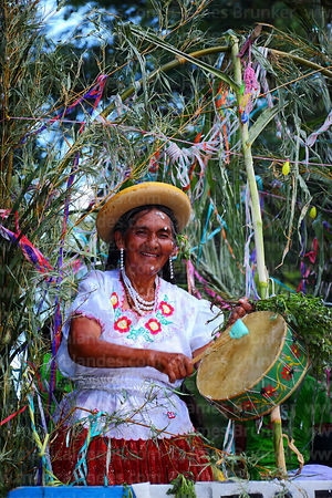 Elderly woman in traditional dress playing caja (drum) at carnival parade, Tarija, Bolivia