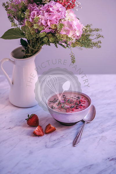 Strawberry smoothie bowl topped with cacao nibs, raspberry powder and rose buds