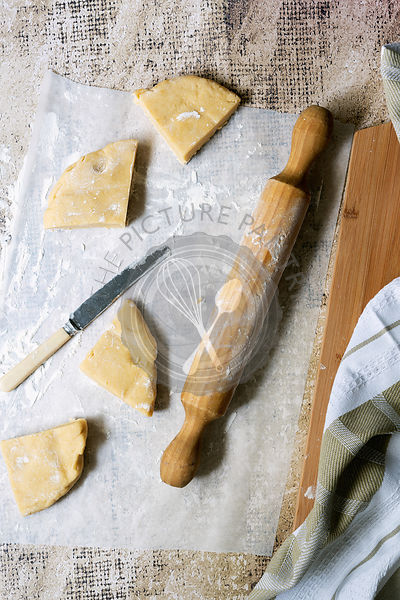 Pieces of homemade shortcrust pastry with a knife and rolling pin on floured baking paper.