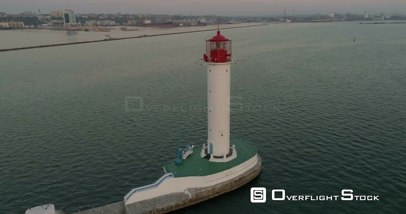 Drone flies around the Odessa Lighthouse at dawn. The cruise terminal and city skyline are in the background. Ukraine