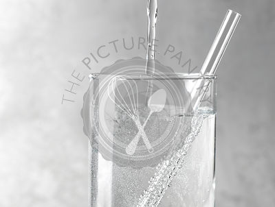 Detail of sparkling water being poured into a clear glass with a clear straw on a gray metal background.